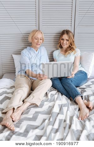 Totally immersed. Beautiful young woman and her senior mother sitting on the bed and being fully concentrated on watching some videos on laptop.