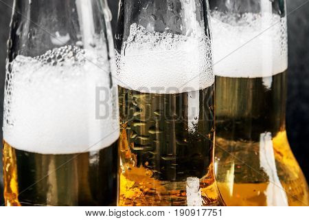 bottles of lager beer and foam background. focus on the middle bottle