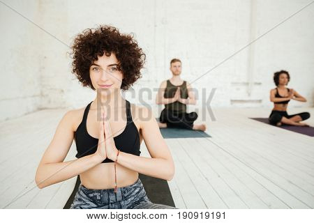 Portrait of young brunette woman looking camera and holding hands compressed while sitting on training mat in gym