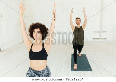 Young caucasian brunette pretty woman with curly hair raising her hands while making exercise in gym