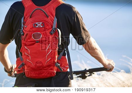 Rear view and close-up of the cyclist standing with mountain bike against river. Young sportsman in the black sportwear and with backpack. Horizontal photo. Travel in the countryside. Concept of the healthy lifestyle.