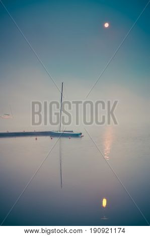 Morning foggy lake landscape. Wooden pier and boat on the lake.