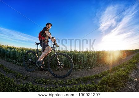 Wide angle of the cyclist standing on the trail on the field against beautiful landscape. Young sportsman in the black sportwear, with backpack and in the helmet. Horizontal photo and fisheye. Concept of the healthy lifestyle.