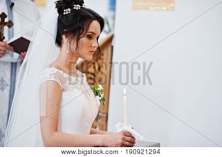 Close Up Photo Of A Beautiful Bride Kneeling In The Church During The Wedding Ceremony Holding A Can