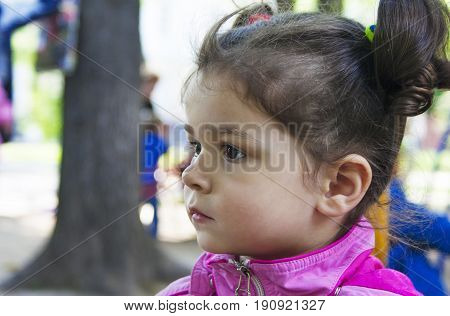 Portrait of a little girl with pigtails in profile. Close-up.