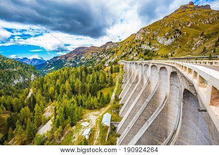 Mountain Lake Lago di Fedaia, Dolomites. Powerful dam blocked the lake. Cool autumn day at Mount Marmolada. The concept of ecological and extreme tourism