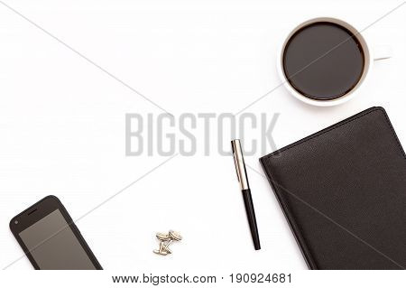 Cup Of Black Coffee, Cufflinks, Phone And A Black Day Planner With Pen On White Background. Minimal