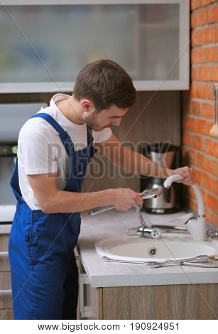 Handsome plumber replacing faucet in kitchen