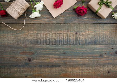 Roses, gift box, craft paper and twine on wood background. Flat lay, top view.