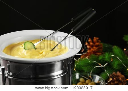 Cucumber slice dipped into cheese fondue on black background