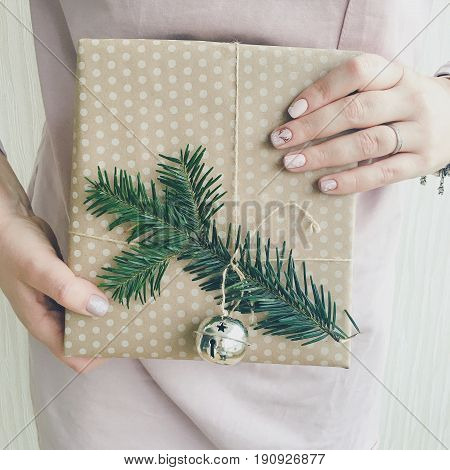 Woman holding a wrapped gift with a branch of a green Christmas tree