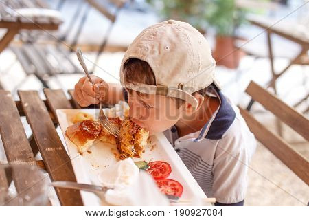 Little angry boy eating junk food in outdoor restaurant