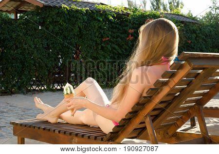 Girl in bikini on deckchair with ice cream in hand