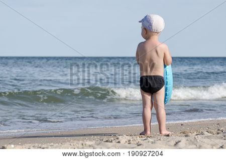 Kid in swimming trunks with a swimming circle stands on the shore of the sea back