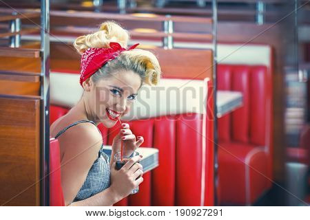 Smiling young woman in retro cafe