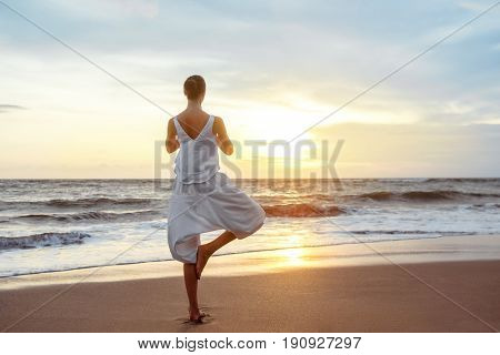 Young woman doing yoga at sunset