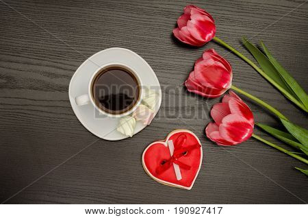 Mug of coffee marshmallows and heartshaped gingerbread three pink tulips. Black background.
