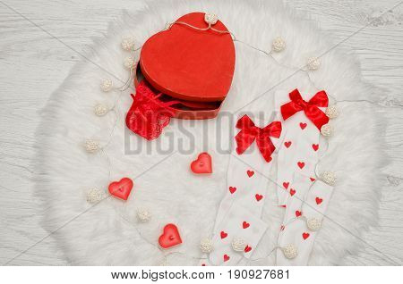 Fashion concept. Red box heart shaped with lace lingerie white stockings with bows heart shaped candles on a white fur.