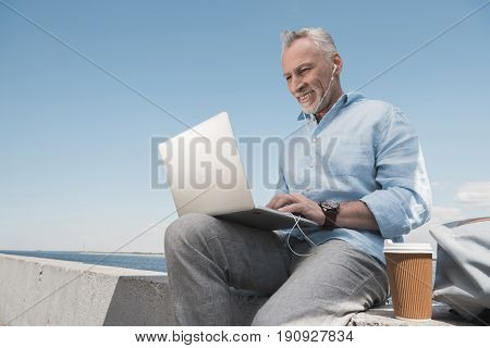 Smiling Grey Haired Man Typing On Laptop While Sitting At Quay