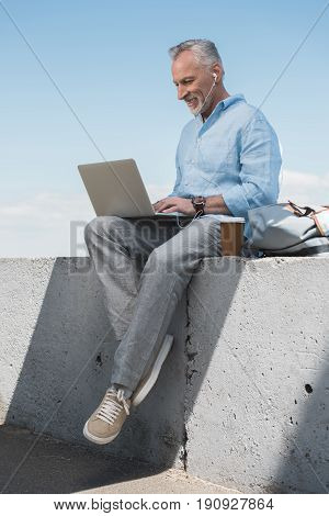 Casual Grey Haired Man Working On Laptop And Listening Music In Earpods Outdoors