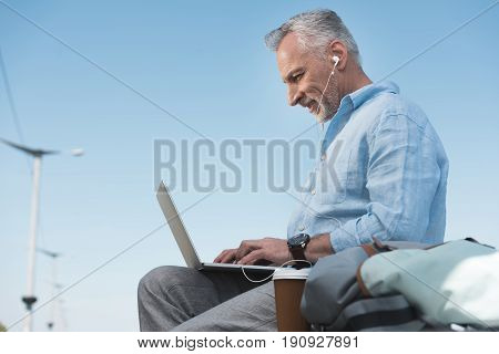 Elderly Man Working On Laptop And Listening Music In Earpods Outdoors