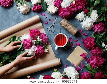 Florist at work: pretty woman making summer bouquet of peonies on a working gray desk. Kraft paper, scissors, string, karkade tea, an envelopeon the table. View from above. Flat lay.