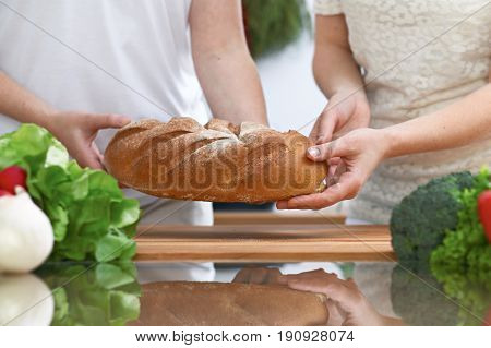 Close-up of human hands slicing bread in a kitchen. Friends having fun while preparing fresh salad. Chef cook represent culinary masterclass. Vegetarian, healthy meal and friendship concept.