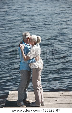 Casual Grey Haired Couple Hugging On Riverside At Daytime