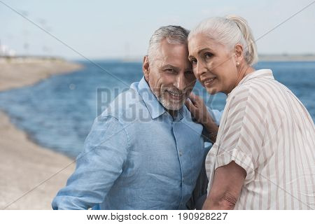 Casual Grey Haired Couple Smiling And Embracing At Quay
