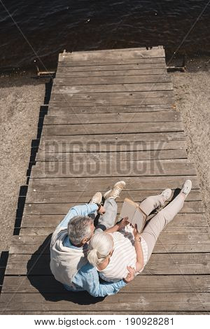 Above View Of Senior Couple Reading Book While Resting On Riverside