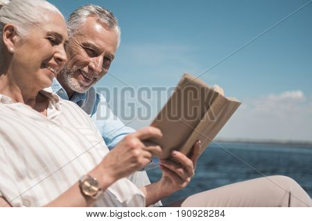 Smiling Elderly Couple Reading Book On The Quay At Daytime