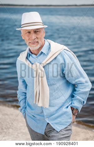 Portrait Of Grey Haired Stylish Man With Hands In Pockets At Riverside