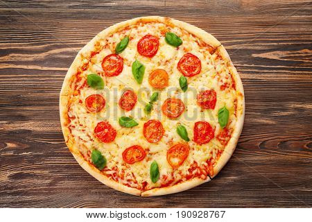 Delicious pizza with tomatoes, basil and melted cheese on wooden background