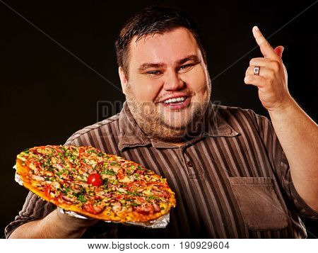 Fat man eating fast food and offers big pizza to customers . Male treats chic junk meal to friends. Breakfast for overweight person. Leads to obesity. Person regularly overeats concept. Cook at home.