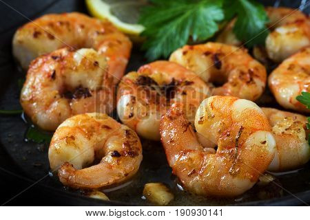 Prawns Shrimps Roasted In A Black Pan With Garlic, Lemon And Italian Parsley Garnish, Close Up