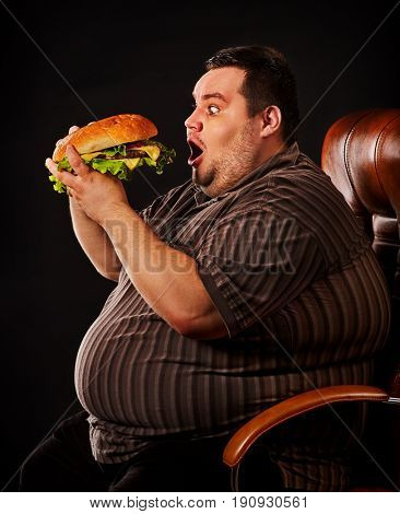 Diet failure of fat man eating fast food hamberger. Happy overweight person spoiled healthy food by greedily eating huge hamburger. Junk meal leads to obesity. Meaning of life in food concept.