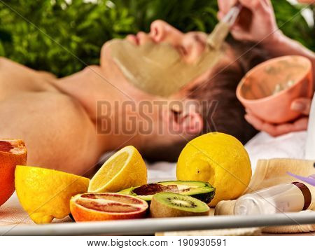 Mud facial mask of man in spa salon. Massage with clay face. Male in therapy room. Apply mask on face with brush. Beautician with bowl therapeutic procedure . Still life with lemons in foreground.