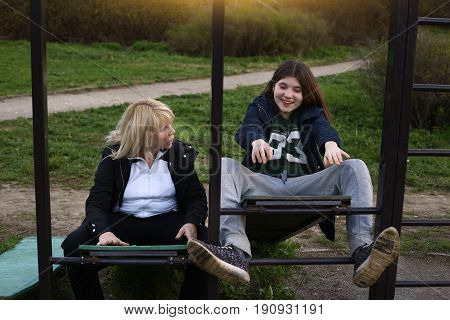 teena girl and woman exercise on outdoor gym place in city park spring photo