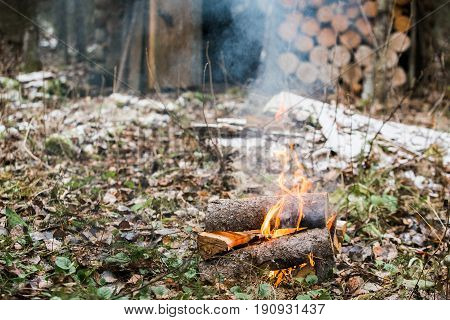 Bonfire, fire. Rest in the woods on a halt. Hunting Lodge. Autumn, cold and cloudy weather, snow.