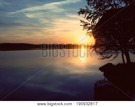 Sun setting by a blue lake under a cloudy sky