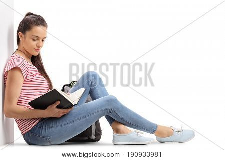 Teenage student leaning against a wall and reading a book isolated on white background