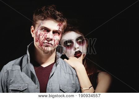 Young people in color contact lenses, with Halloween makeup on black background