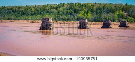 Muddy river with abandon bridge pillars Nova Scotia
