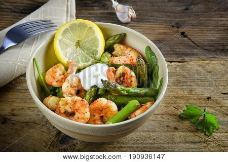 Salad From Prawn Shrimp, Green Asparagus, Arugula, Garlic, Parsley And Lemon Slice In A Bowl On A Ru