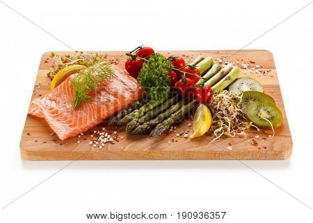 Fresh raw salmon with asparagus on cutting board on white background