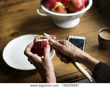 Closeup of hand with knife peeling apple
