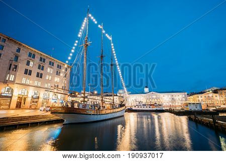 Helsinki, Finland - December 9, 2016: Old Wooden Sailing Vessel Ship Schooner Is Moored To The City Pier, Jetty. Unusual Cafe Restaurant In City Center In Lighting At Evening Or Night Illumination