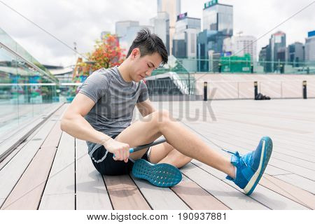 Man using roller stick on his legs to relief pain