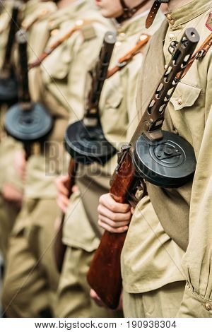 Re-enactos Dressed As Russian Soviet Soldiers Of World War II Holds Sub-machine Guns Weapon In Hands And Standing Order.