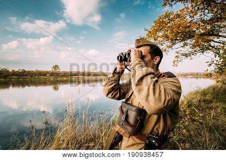 Dyatlovichi, Belarus - October 1, 2016: Reenactor Man Dressed As Russian Soviet Red Army Infantry Soldier Of World War II Looking At Old Army Military Binoculars In Meadow At Historical Reenactment